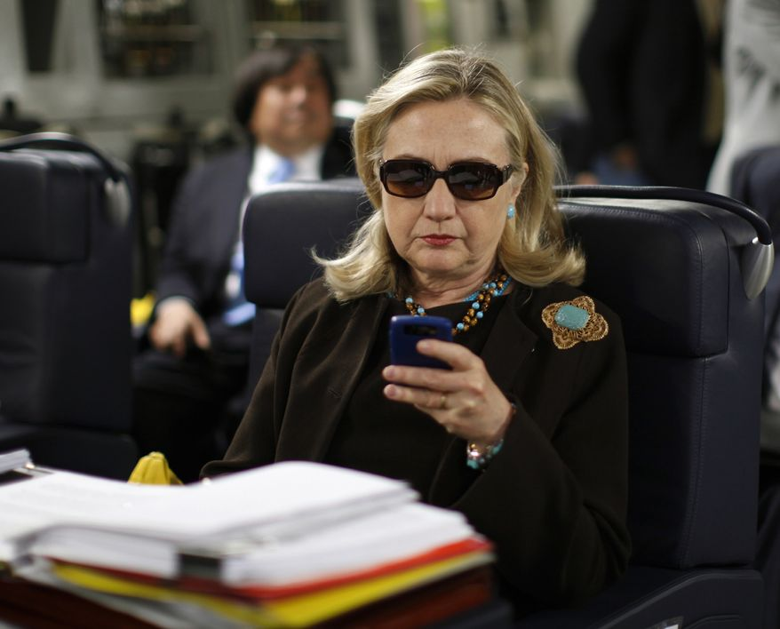 Then-Secretary of State Hillary Rodham Clinton checks her Blackberry from a desk inside a C-17 military plane upon her departure from Malta, in the Mediterranean Sea, bound for Tripoli, Libya, on Oct. 18, 2011. (AP Photo/Kevin Lamarque, Pool, File) ** FILE **