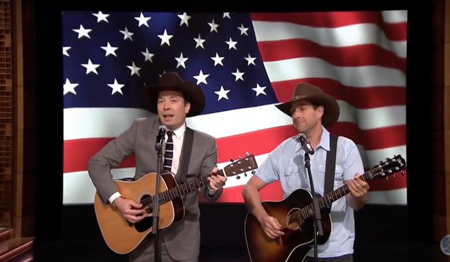 "Jimmy Fallon (l) and guest Adam Sandler (r) serenade the May 25, 2016 audience of ""The Tonight Show"" with a tribute to U.S. servicemen entitled ""Friends On All Bases,"" a parody of Garth Brooks's ""Friends In Low Places."" Screen capture from a ""Tonight Show"" YouTube video. Accessed May 26, 2016."