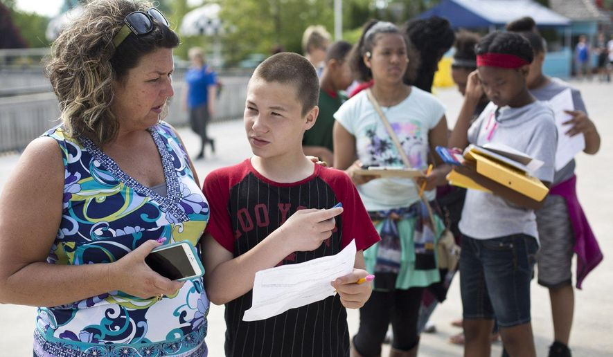 Kathy Jo Stevens helps Oak View student Neven McCustion with his physics packet during physics day at Michigan's Adventures in Muskegon, Mich. on  May 25, 2016. More than 450 students from 12 schools had the opportunity to spend the day applying mathematics, physics and measuring skills to solve problems in a real-world setting at Michigan's Adventure. (Emily Brouwer/Muskegon Chronicle via AP) ALL LOCAL TELEVISION OUT; LOCAL TELEVISION INTERNET OUT; MANDATORY CREDIT