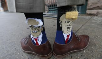 Colorado Gov. John Hickenlooper shows off his socks--one with Democratic presidential candidate Bernie Sanders and the other with Republican candidate Donald Trump--before entering his former brewpub for a book signing event to mark the release of his autobiography Thursday, May 26, 2016, in Denver. (AP Photo/David Zalubowski)