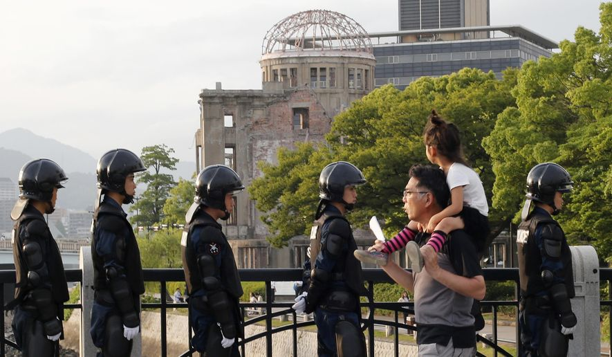 With the Atomic Bomb Dome as a backdrop, passers-by move past riot police near Hiroshima Peace Memorial Museum in Hiroshima, southwestern Japan, Thursday, May 26, 2016. U.S. President Barack Obama is to visit Hiroshima on Friday, May 27 after the Group of Seven summit in central Japan, becoming the first serving American president to do so. (AP Photo/Shuji Kajiyama)