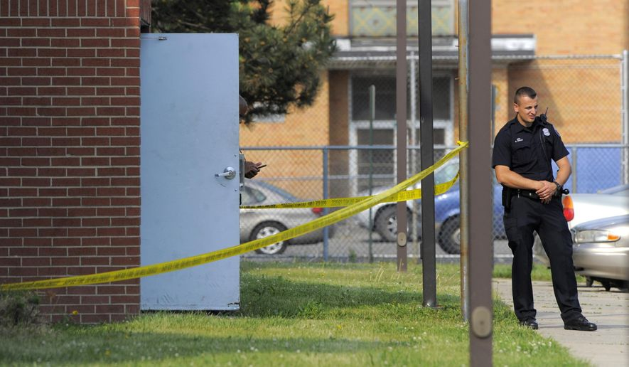 A Detroit Police officer stands near the entrance of an apartment, Wednesday May 25, 2016, after a child was found dead inside in Detroit.  Police say the boy, age 2 to 3, may have been dead for more than a week before his body was found Wednesday by a maintenance worker who noticed a strong odor.  (Steve Perez/Detroit News via AP)  DETROIT FREE PRESS OUT; HUFFINGTON POST OUT; MANDATORY CREDIT