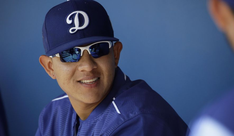 FILE - In this March 14, 2016, Los Angeles Dodgers pitcher Julio Urias smiles while talking to teammates in the dugout during a spring training baseball game against the Milwaukee Urias, 19, is set to make his highly anticipated major league debut for the Dodgers on Friday night, May 27, 2016, in New York against the Mets (AP Photo/Jae C. Hong, File)