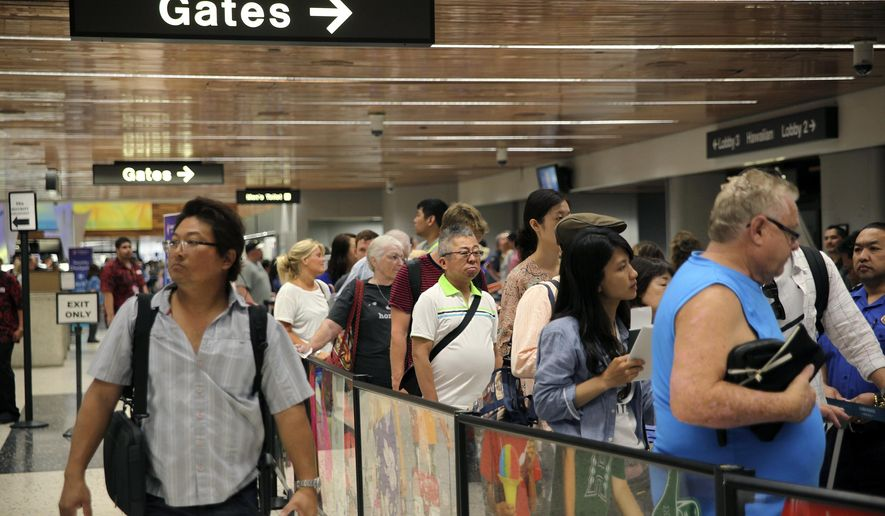 Travelers wait in security checkpoint lines at Honolulu International Airport on Thursday, May 26, 2016, in Honolulu. Hawaiian Airlines says passengers should expect longer wait times than usual over the busy Memorial Day weekend because the Transportation Security Administration will have two less canine units than usual. (AP Photo/Marina Riker)