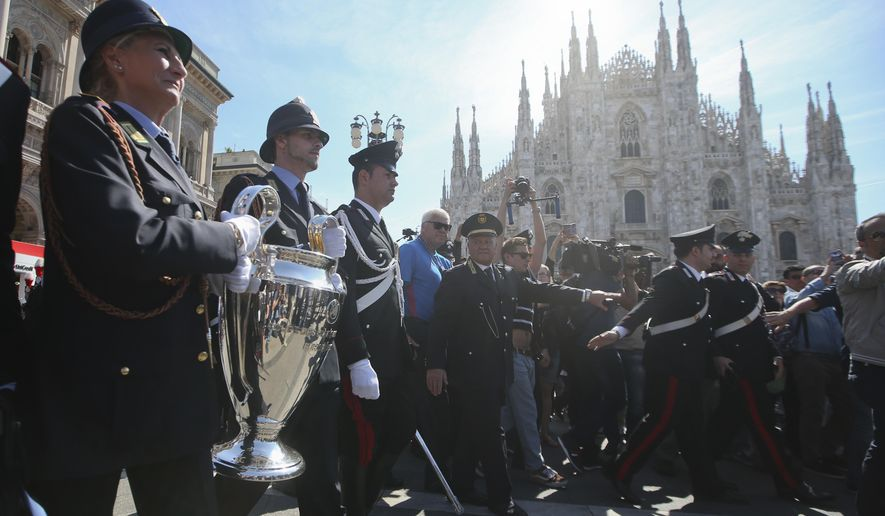 Local police officers hold the Champions League trophy in front of the Duomo gothic cathedral, during the unveiling of the Champions Festival event, in Milan, Italy, Thursday, May 26, 2016. The Champions League soccer final between Real Madrid and Atletico Madrid will be held at the San Siro stadium on Saturday, May 28, 2016. (AP Photo/Luca Bruno)