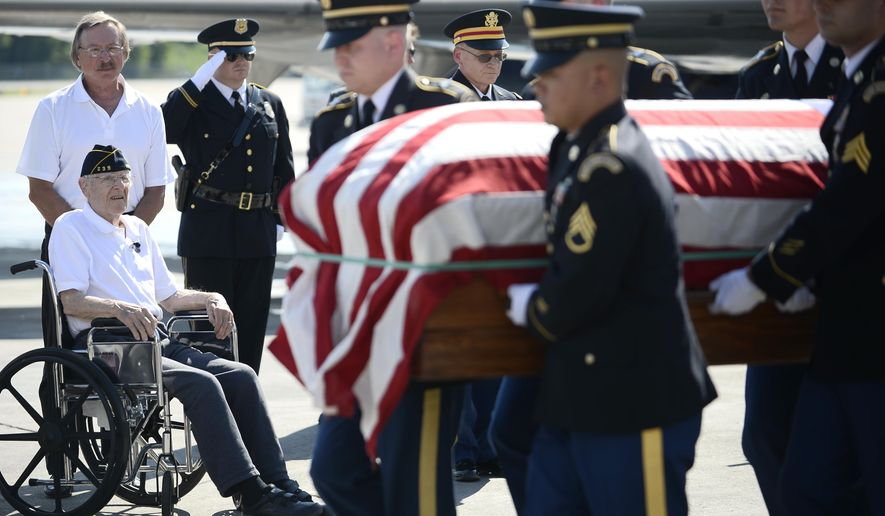 In this Tuesday, May 24, 2016 photo, Paul Sersha, bottom left, 97, and his son, Tom, back, watch as members of the Minnesota Army National Guard Honor Guard carried a casket with the remains of Paul's brother, John P. Sersha, from a passenger jet to a hearse during a planeside honors ceremony at St. Paul Airport in Minneapolis. Remains of a soldier from the Iron Range killed during World War II were recently identified and will reach their final resting place on Memorial Day weekend. (Aaron Lavinsky/Star Tribune via AP) MANDATORY CREDIT