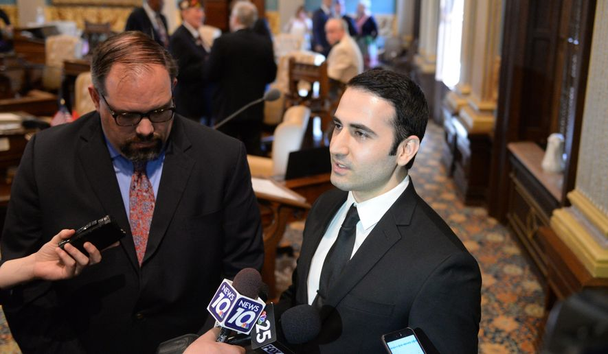State Senator Jim Ananich, D-Flint, left, listens as Amir Hekmati speaks to the media in the Michigan Senate Chamber on Thursday, May 26, 2016, in Lansing, Mich. Hekmati is a former United States Marine who was detained in August 2011 in Iran on espionage charges. (Julia Nagy/Lansing State Journal via AP)  NO SALES; MANDATORY CREDIT