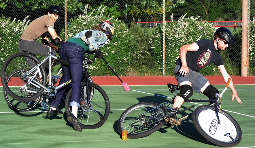In this photo taken May 16, 2016, Nicholas Lidtke, left, reacts as Emily Cureton, center, collides with John Mattingly, right, bending Mattingly's rear tire and sending him off his bicycle, during a bicycle polo match in Ashland, Ore. (Denise Baratta/Medford Mail Tribune via AP) MANDATORY CREDIT