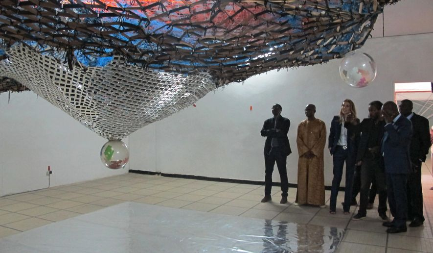 "In this photo taken Monday May. 9, 2016 Simon Njami, Artistic Director of the 12th Edition of the Dakar Biennele, Dak'Art 2016, shows visitors an installation by Akiresh Akindiya entitled ""Portraits"" in Dakar, Senegal. Videos projected onto massive buildings, pop up art galleries and installations in an old courthouse are features of the Dakar Biennale, Africa's largest contemporary art festival currently enlivening Senegal's capital. (AP Photo/Carley Petesch)"