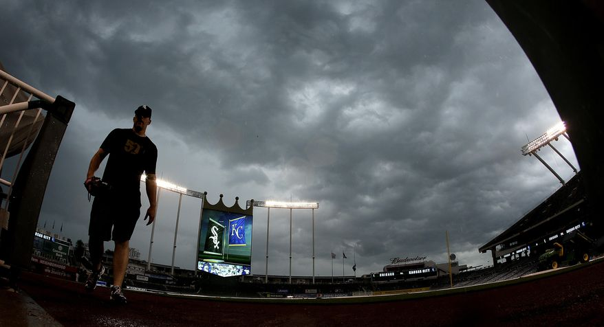 A player for the Chicago White Sox heads for the dugout as a thunderstorm moves over Kauffman Stadium before a baseball game against the Kansas City Royals on Thursday, May 26, 2016, in Kansas City, Mo. The game was postponed due to rain. (AP Photo/Charlie Riedel)