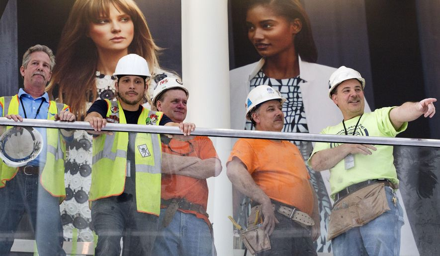 Union construction workers participate in the opening of the east end of the World Trade Center Transportation Hub,Thursday, May 26, 2016, in New York. Behind them are advertisements for a clothing store, which will be a part of a gallery of stores in the hub. (AP Photo/Mark Lennihan)