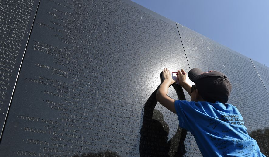 Zack Drake, 11, from Crab Orchard, W. Va., takes a rubbing of a name from the Vietnam War Memorial in Washington, Friday, May 27, 2016. The visit was part of the Crab Orchard Elementary School visit to Washington, on the start  of the Memorial Day weekend. (AP Photo/Susan Walsh)