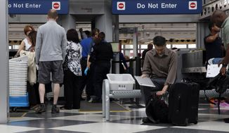 Travelers pass through a Transportation Security Administration checkpoint at O'Hare International Airport, Friday, May 27, 2016, in Chicago. Memorial Day weekend, the unofficial start of summer vacations for many and a busy travel period, serves as a crucial test for the TSA. (AP Photo/Kiichiro Sato)