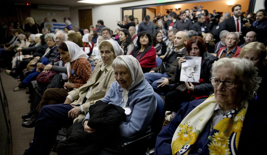 People sit in federal court for the sentencing of former military officers in Buenos Aires, Argentina, Friday, May 27, 2016. The court will deliver a sentence on a long-awaited human rights trial focused on Operation Condor, a secret conspiracy launched by six South American dictators in the 1970s in a combined effort to track down their enemies and eliminate them. (AP Photo/Natacha Pisarenko)