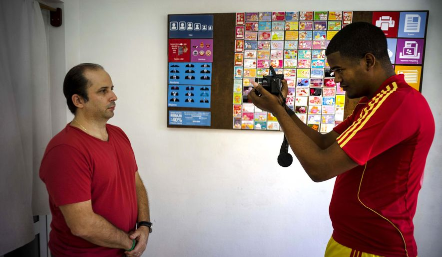 Lian Marrero takes a portrait of his client, Miami-based Cuban Javier Fontanella, for his Cuban citizenship application in Havana, Cuba, Thursday, May 26, 2016. Marrero, a 27-year-old electrician who runs a busy photo studio in the front room of the home he shares with his wife, said he offered clients actual clothing to try on but people found it unappealing to wear clothes that others had been sweating in. So he digitally cuts away his clients' shirts with a photo-editing program and pastes in formal suits. (AP Photo/Ramon Espinosa)