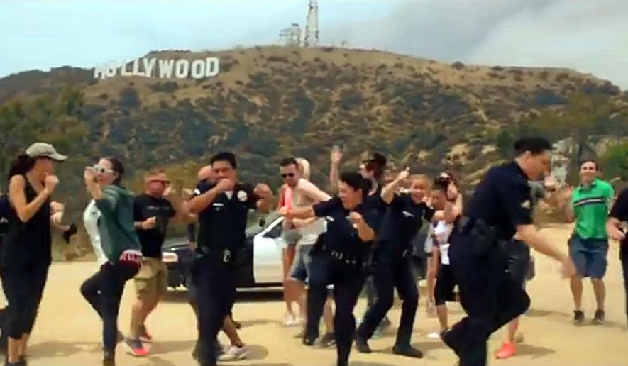 "In this undated frame from video provided by the Los Angeles Police Department, LAPD officers and others dance beneath the iconic Hollywood Sign in Los Angeles. In a now-viral sensation, police officers across the U.S. are dancing an updated version of the running man to a catchy 1990s hip hop song, ""My Boo"" by Ghost Town DJ's, in videos that have included professional sports mascots, cheerleading squads and at least one explosion. The videos started with the New York Police Department and are getting more elaborate and popular, with even some police chiefs joining in. (Los Angeles Police Department via AP) MANDATORY CREDIT"