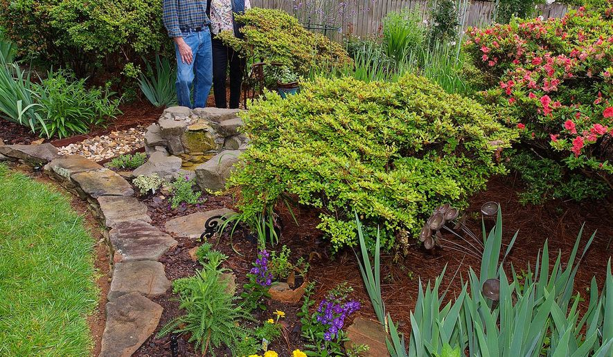 In this May 19, 2016 photo, Larry Cravey and wife Sandra Kessler stand by a water feature in one of their flower gardens at their home on Sequoia Drive in Lexington, N.C. Their garden along with five other gardens by local residents will be featured on the Davidson County Master Gardener Volunteer Association's 12th Annual Garden Tour on June 4-5. (Donnie Roberts/The Dispatch via AP) MANDATORY CREDIT