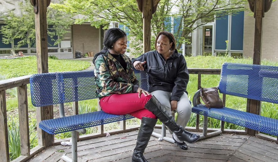 In this May 4, 2016, photo, Kelly Edwards, right, who has been mentoring Tianna Lee for about the past nine years, enjoys some time with the Centennial High School senior in the school's courtyard in Champaign, Ill. As a fourth-grader at Booker T. Elementary School, Lee entered the C-U One-to-One Mentoring program, where she was linked with Edwards. (Heather Coit/The News-Gazette via AP)  MANDATORY CREDIT