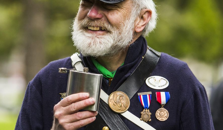 ADVANCE FOR USE SUNDAY, MAY 29 - In this photo taken Saturday, May 14, 2016, Birch Run, Mich., resident Bob Boquette, of the 14th Michigan Volunteer Infantry of the Sons of Union Veterans of the Civil War, takes a sip from a flask as it is passed around a circle during a ceremony in honor of Boquette's great-great-grandfather Alvah Nichols, a Civil War soldier whose grave was recently discovered by his descendants at Riverside Cemetery in St. Charles, Mich. (Katy Kildee/The Saginaw News via AP) ALL LOCAL TELEVISION OUT; LOCAL TELEVISION INTERNET OUT; MANDATORY CREDIT