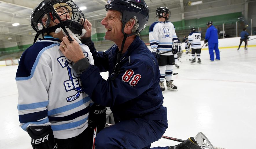 In a Monday, April 25, 2016 photo, Rich Garrison, right, laughs, as he tries to get underneath the helmet cage to wipe the nose of Myles Miller, during practice for the York Polar Bears hockey team, in York, Pa. Garrison of Spring Grove, and a member of the USA Warriors hockey team, established the team for special needs children like Myles, who has autism.    (Jason Plotkin/York Daily Record via AP)  YORK DISPATCH OUT; MANDATORY CREDIT