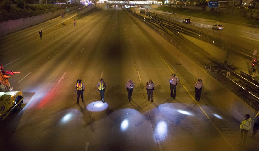 In this Friday, May 20, 2016 photo, members of the Illinois State Police search for evidence at the scene of a shooting on the north bound lanes of the Dan Ryan Expressway between 87th and 95th Street, in Chicago. A rash of shootings on Chicago area expressways has authorities promising that they will keep an especially close eye on the roadways on the Memorial Day weekend.  (Armando L. Sanchez /Chicago Tribune via AP) MANDATORY CREDIT CHICAGO TRIBUNE; CHICAGO SUN-TIMES OUT; DAILY HERALD OUT; NORTHWEST HERALD OUT; THE HERALD-NEWS OUT; DAILY CHRONICLE OUT; THE TIMES OF NORTHWEST INDIANA OUT; TV OUT; MAGS OUT; NO SALES