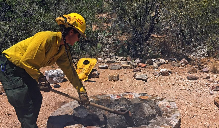 In this Tuesday, May 24, 2016 photo, U.S. Forest Service firefighter Kristina Rask of the Santa Catalina District demonstrates how to properly put out a campfire at Sabino Canyon in Tucson, Ariz. The Memorial Day holiday weekend routinely is among the busiest of the year at recreation sites around Arizona. The lack of fire restrictions for a second year in a row at this time comes thanks to the amount of moisture in fuels. But that doesn't mean officials aren't worried about embers escaping from campfires and potentially starting a wildfire. The Coconino National Forest counted more than 600 abandoned campfires last year and they're popping up by the dozens each week in other areas.  (AP Photo/Astrid Galvan)