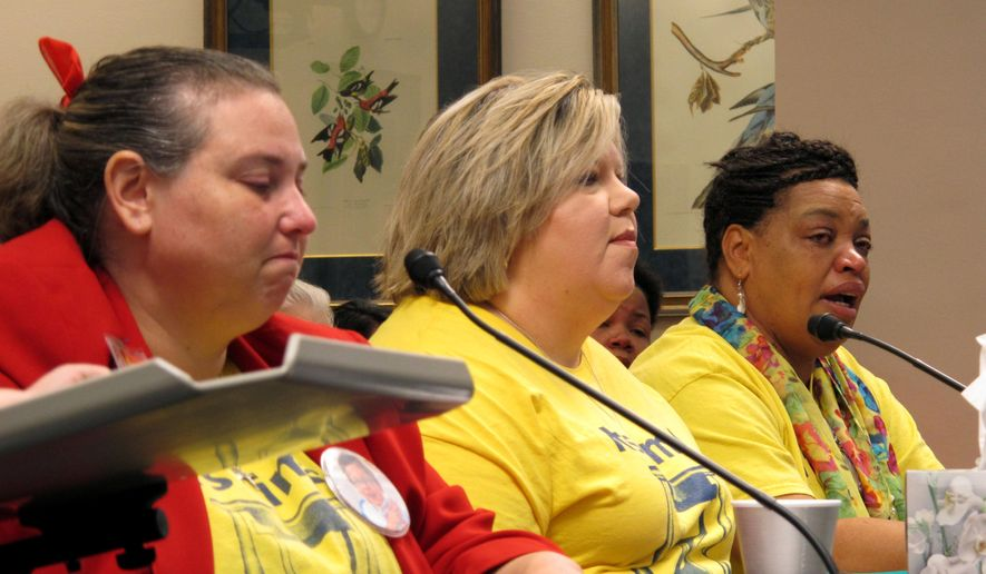 Elaine Harmon of Lake Charles, right, cries as she and other parents who rely on the state for health care services for their children with developmental disabilities ask the Senate Finance Committee to shield the programs from cuts, on Friday, May 27, 2016, in Baton Rouge, La. (AP Photo/Melinda Deslatte)