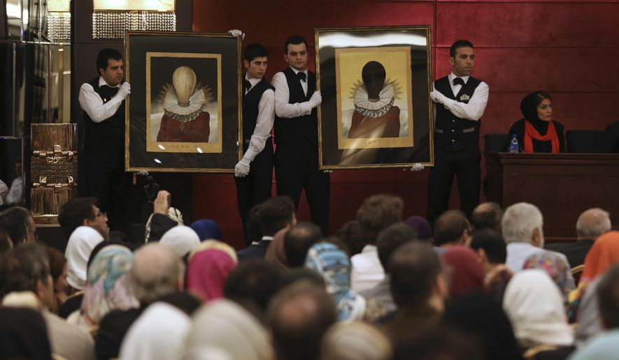 Iranian auction workers hold a pair of paintings of Iranian artist Aydin Aghdashlou in Tehran Art Auction at the Azadi Hotel in Tehran, Iran, Friday, May 27, 2016. (AP Photo/Vahid Salemi)