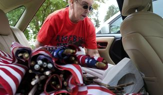 Barbara Morris get the base for an angel she places facing hundreds of crosses and flags in the grassy lawn in front of the Fort Bragg Harley -Davidson Motorcycles dealership Monday, May 23, 2016, in Fayettville, NC.. It's an annual Memorial Day tribute. (Raul R. Rubiera/The Fayetteville Observer via AP). MAGS OUT. NO SALES. MANDATORY CREDIT; DUNN DAILY RECORD OUT; THE ROBESONIAN OUT