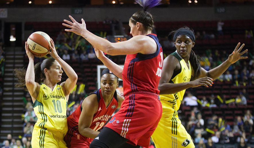 Seattle Storm guard Sue Bird, left, tries to work around Washington Mystics guard Ivory Latta (12) and center Stefanie Dolson as Storm forward Crystal Langhorne, right, looks over during the first half of a WNBA basketball game Thursday, May 26, 2016, in Seattle. (Lindsey Wasson/The Seattle Times via AP)