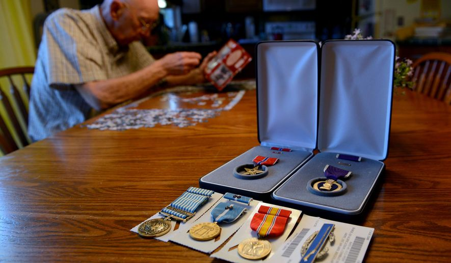 Bob Flory puts together a puzzle at his home Monday, May 23, 2016, in Holt, Mich. Flory, 84, is a Korean War veteran and recently received a Purple Heart he thought was stolen along with a Bronze Star and other medals he didn't know he qualified for.  (Dave Wasinger/Lansing State Journal via AP)  NO SALES; MANDATORY CREDIT