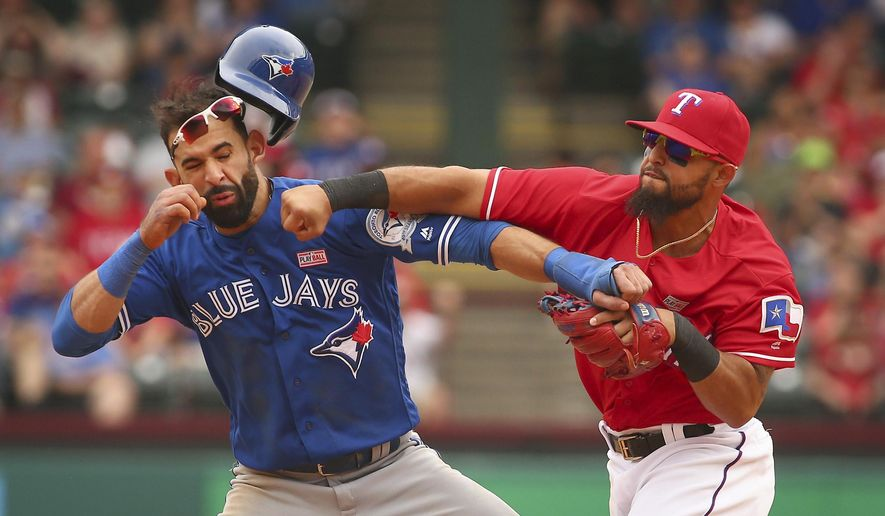 FILE - In this May 15, 2016, Toronto Blue Jays' Jose Bautista, left, is hit by Texas Rangers second baseman Rougned Odor, right, after Bautista slid into second in the eighth inning of a baseball game at Globe Life Park in Arlington, Texas. Odor's suspension for punching Bautista was reduced to seven games, and the Texas second baseman started serving it Friday, May 27, 2016. (Richard W. Rodriguez/Star-Telegram via AP, File) MAGAZINES OUT (FORT WORTH WEEKLY, 360 WEST); INTERNET OUT; MANDATORY CREDIT