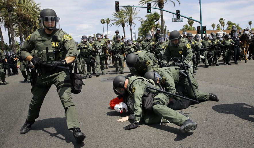 FILE - In this May 25, 2016 file photo, Orange County Sheriff's deputies take a protester into custody near the Anaheim Convention Center where Republican presidential candidate Donald Trump held a rally in Anaheim, Calif. Two California cities are gearing up for visits by Trump and the possibility of protests, following similar events around the country that led to violence and several arrests. The presumptive Republican presidential nominee is speaking Friday, May 27, 2016, in Fresno and San Diego ahead of California's June 7 primary election. (AP Photo/Jae C. Hong, File)