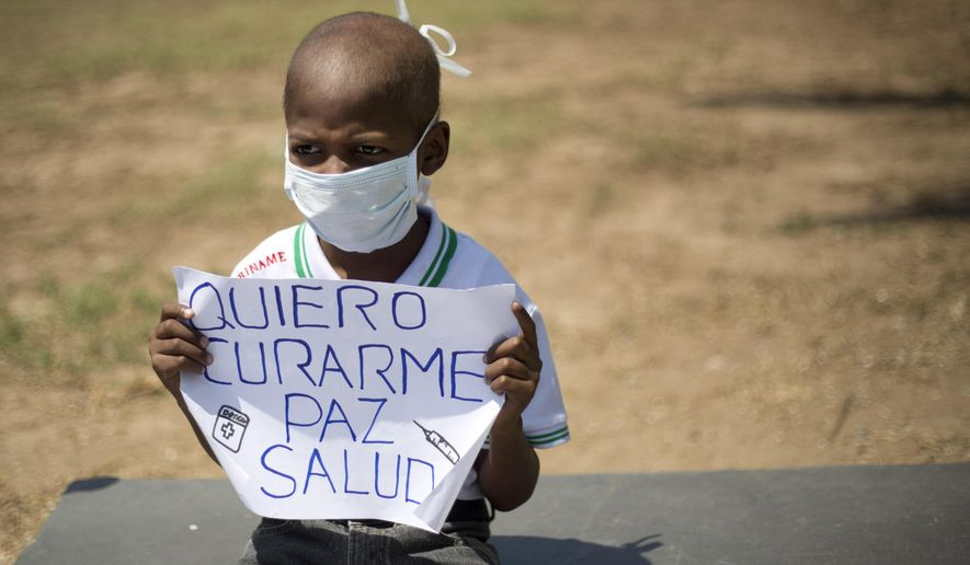 "FILE - In this Feb. 26, 2016 file photo, Oliver Sanchez, diagnosed with non-Hodgkin's lymphoma, holds a sign with a message that reads in Spanish; ""I want to be cured, peace, health"" during a protest against the growing shortage of medicines and medical supplies, in Caracas, Venezuela. The eight-year-old boy who had become a symbol of Venezuela's medical crisis, died Tuesday, May 24, 2016. (AP Photo/Ariana Cubillos, File)"