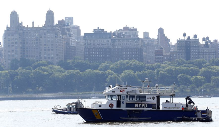NYPD search and rescue boats sit on the Hudson River near the site of small plane crash, Saturday, May 28, 2016, in North Bergen, N.J. A World War II vintage P-47 Thunderbolt aircraft crashed into the river Friday, May 27, 2016, killing its pilot. (AP Photo/Julio Cortez)
