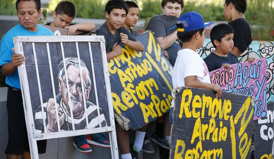 Protesters rally in front of Maricopa County Sheriff's Office Headquarters Wednesday, May 25, 2016, in Phoenix. Arizona taxpayers could be paying out to compensate hundreds of Latinos who were illegally detained when Sheriff Joe Arpaio rounded them up in past immigration patrols. (AP Photo/Ross D. Franklin)