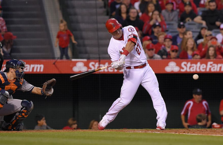 Los Angeles Angels' Mike Trout, right, hits a two-RBI double as Houston Astros catcher Jason Castro watches during the third inning of a baseball game, Friday, May 27, 2016, in Anaheim, Calif. (AP Photo/Mark J. Terrill)