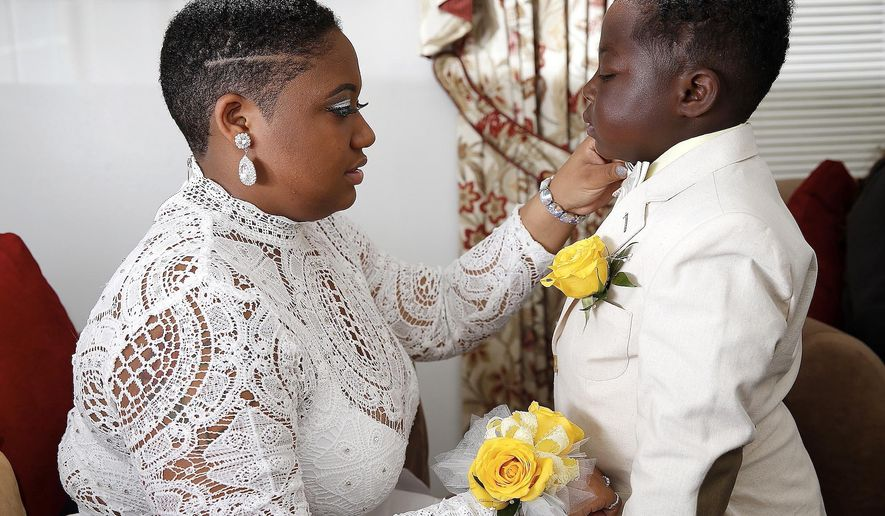 ADVANCED FOR RELEASE SATURDAY, MAY 28, 2016 Sha'nayia Johnson, 18, a senior at Washington and Lee High School in Westmoreland County, gets ready with her little brother, JJ Brown, 7, to go to her senior prom at the Riverboat in Colonial Beach. JJ was diagnosed with neuroblastoma as a toddler. He has had 56 blood transfusions and 6 different chemotherapy sessions since being diagnosed. In March, doctors told his mom that JJ was cancer free. To celebrate, his big sister is taking him to prom. (Suzanne Carr Rossi/The Free Lance-Star via AP)