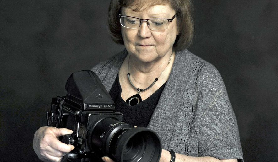 In this photo taken May 11, 2016, Maureen Powers, owner of Buckroyd Studio, poses with her old medium format film camera in her studio in Fort Dodge, Iowa. Digital photography, and the ability to work with the images on computers, began to reach into the studios as the '90s were ending. While Powers still owns the film cameras she once used for portraits, they now spend their time in a cabinet rather than on location. (Hans Madsen/The Messenger via AP) MANDATORY CREDIT
