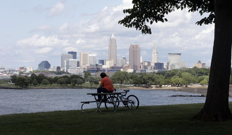 FILE - In this July 8, 2014, file photo, a man sits on a picnic table with a view of downtown Cleveland.  City officials plan to present an overview of security preparation Tuesday, May 31, 2016, for this summer's Republican National Convention in Cleveland, seeking to counter continuing concerns about readiness to host the event expected to bring 50,000 visitors to northeast Ohio. (AP Photo/Tony Dejak, File)