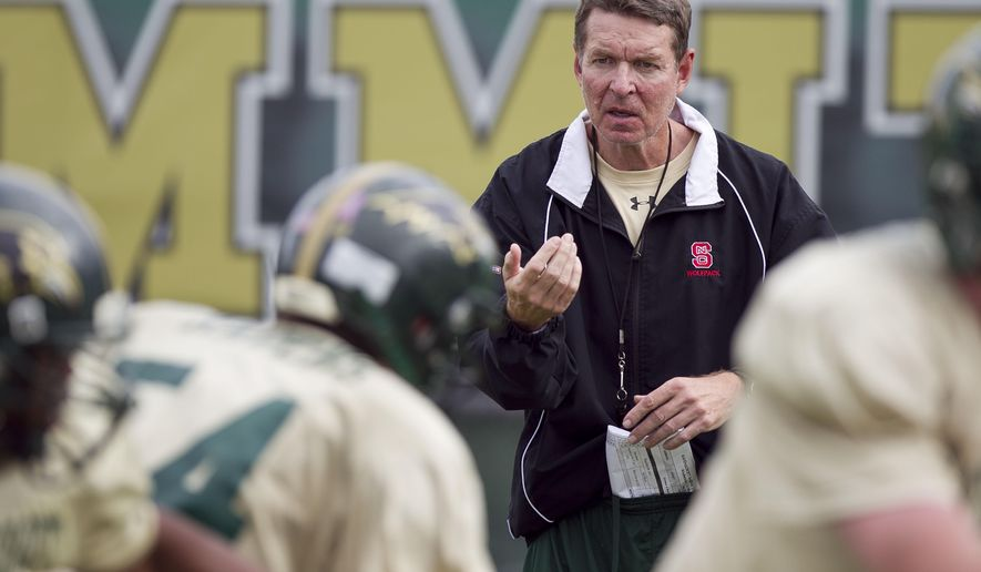 In this photo taken Oct. 16, 2013, Ravenscroft assistant football coach Don Horton works with the offensive line during high school football practice in Raleigh, N.C. Horton, a former North Carolina State and Boston College assistant football coach who fought a public battle with Parkinson's disease, died Saturday, May 28, 2016. He was 58. (Robert Willett/The News & Observer via AP) MANDATORY CREDIT