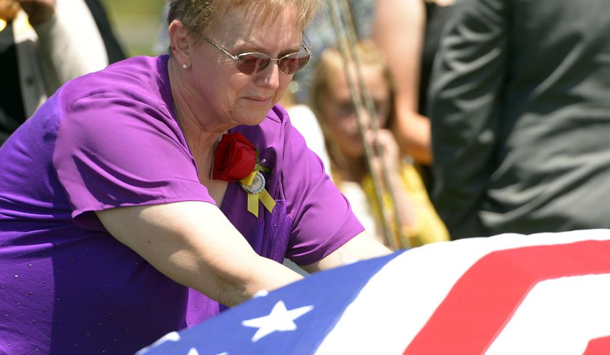 Lorie Ricks lingers for a moment at the casket of her husband, Utah Transit Authority electrician Kay Ricks, 63, who was laid to rest Saturday, May 28, 2016, at Lehi City Cemetery. Ricks served in the Navy and was a veteran of the Vietnam War, 4 years active duty and 2 years in the Naval Reserve and 8 years in the Utah National Guard. Utah police continue gathering evidence that could link two men who fled to Wyoming, after tying up and assaulting a mother and her four teenage daughters in a Centerville home on May 10, to the slaying of Ricks employee whose body was found in rural Wyoming. (Leah Hogsten /The Salt Lake Tribune via AP)
