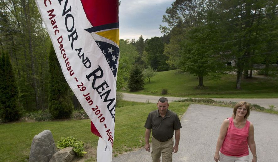 In this photo taken Wednesday May 25, 2016 Mark and Nancy Decoteau walk up their driveway in Thornton, N.H. The Decoteau's son SPC Marc Decoteau was killed in Afghanistan on Jan. 29, 2010. His name along with 49 others will be unveiled on Memorial Day on a new memorial at the state's Veterans Cemetery honoring men and woman killed since 9/11. (AP Photo/Jim Cole)