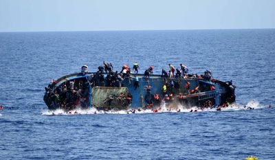 In this May 25, 2016, file photo made available by the Italian Navy, people try to jump in the water right before their boat overturns off the Libyan coast. Over 700 migrants are feared dead in three Mediterranean Sea shipwrecks south of Italy in the last few days as they tried desperately to reach Europe in unseaworthy smuggling boats, the U.N. refugee agency said Sunday, May 29, 2016. (Italian navy via AP Photo, file)