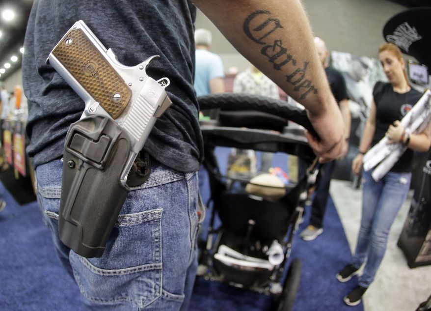 A man wears his handgun in a holster as he pushes his son in a stroller at the National Rifle Association Convention in 2016. (Associated Press)