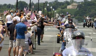 Participants in the Rolling Thunder annual motorcycle rally ride past Arlington memorial bridge as they salute a crowd, during the annual Rolling Thunder parade ahead of Memorial Day in Washington, Sunday, May 29, 2016. (AP Photo/Jose Luis Magana)