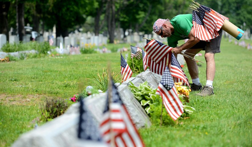 Norman Makoujy of Totowa, N.J., places flags on the graves of Veterans at Holy Sepulchre Cemetery in Totowa Memorial weekend Sunday, May 29, 2016. Makoujy volunteers his time to place the flags, putting 35 dozen flags with volunteers on Saturday and 150 flags on Sunday. Makoujy recovers flags from the cemetery after July 4th and  recycles them the next year.  (Amy Newman/The Record of Bergen County via AP)