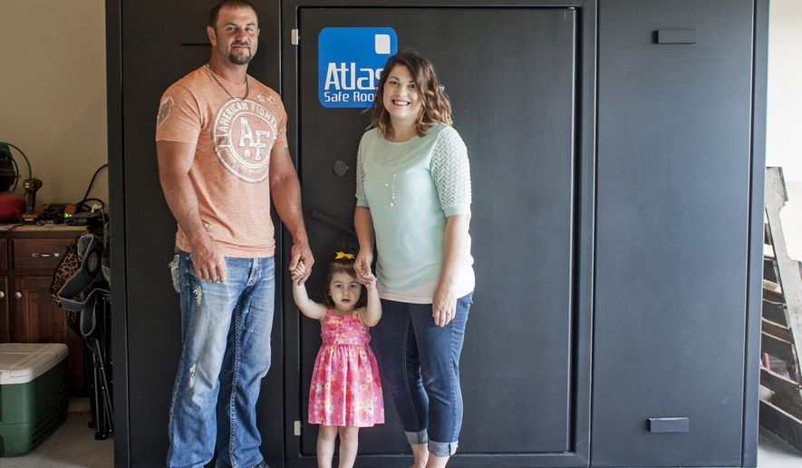 In this Thursday, May 26, 2016, photo provided by Jason T. Williams, Ricky and Kayla Smith and their 2-year-old daughter Kailee pose in front of the tornado safe room built in their garage in Joplin, Mo., shortly after they got married in 2013. The couple was able to pay for the safe room with wedding gift donations. A trend in tornado-prone areas of the Midwest and South are for engaged couples to use their wedding registries and word of mouth to seek safe room donations instead of the typical gifts such as kitchen appliances or other household goods. (Jason T. Williams via AP)