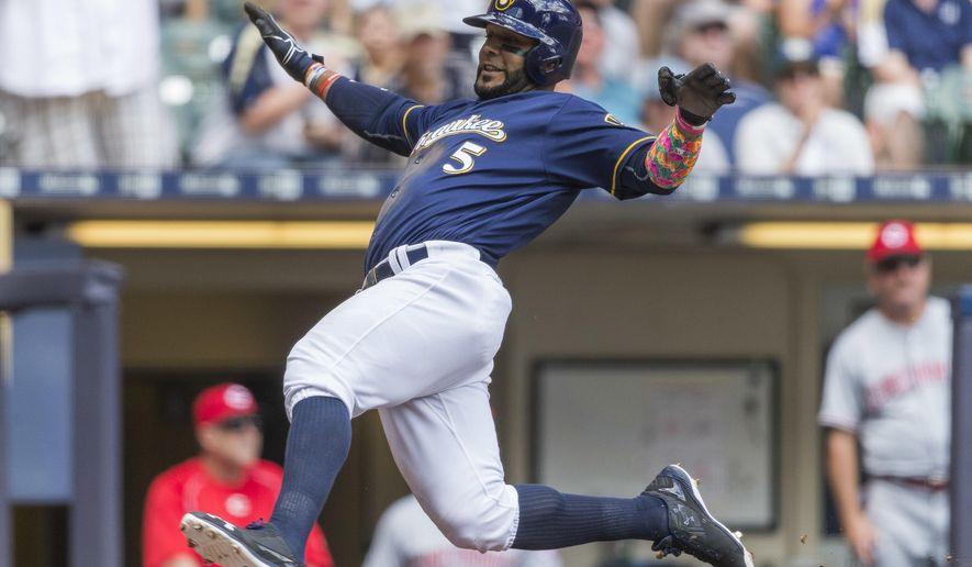 Milwaukee Brewers' Jonathan Villar prepares to slide home to score off a Hernan Perez double against the Cincinnati Reds during the third inning of a baseball game Sunday, May 29, 2016, in Milwaukee. (AP Photo/Tom Lynn)