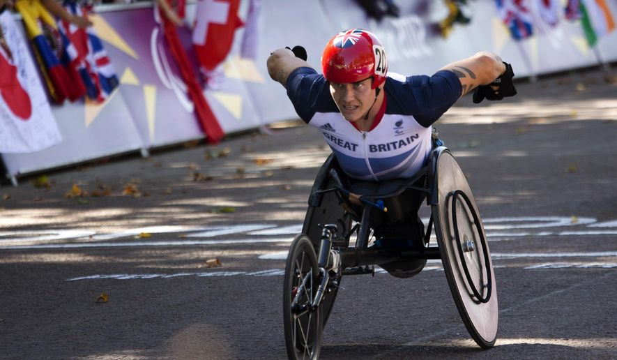 FILE - In this file photo dated Sunday, Sept. 9, 2012, Great Britain's David Weir wins the men's marathon T54 category at the 2012 Paralympics, Sunday, Sept. 9, 2012, in London. Six-time Paralympic gold-medalist David Weir became the first wheelchair racer to complete a mile under three minutes on Sunday, May 29, 2016, finishing the Westminster Mile in a time of 2 minutes, 57 seconds, beating his previous best by six seconds. (AP Photo/Emilio Morenatti, FILE)